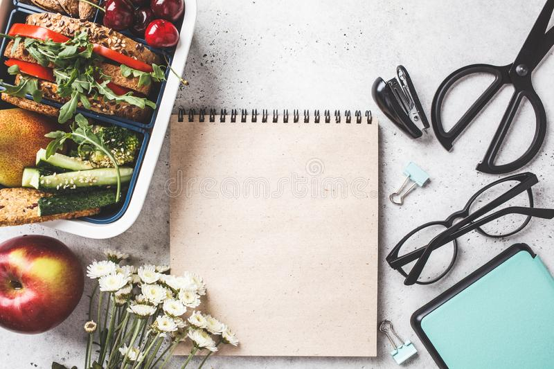 Back to school concept.  Lunch box with sandwich, fruit, snacks, notebook, pencils and school items, top view royalty free stock image