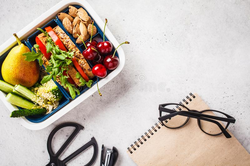 Back to school concept.  Lunch box with sandwich, fruit, snacks, notebook, pencils and school items, top view stock photo