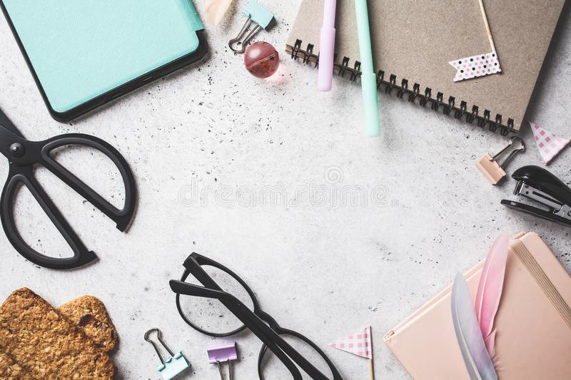 Back to school concept.  Notebook, glasses, pens and stationery objects on a gray background, top view royalty free stock photography