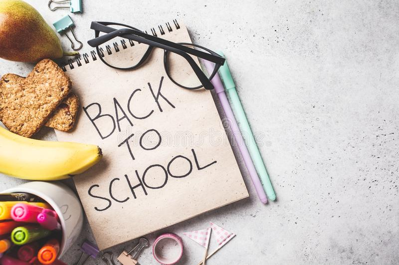 Back to school concept.  Notebook, glasses, pens and stationery objects on a gray background, top view royalty free stock photos