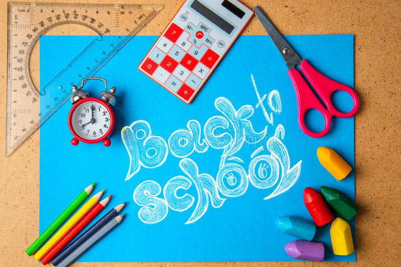 Back to school concept. Old alarm clock on the background with school supplies.  royalty free stock photo