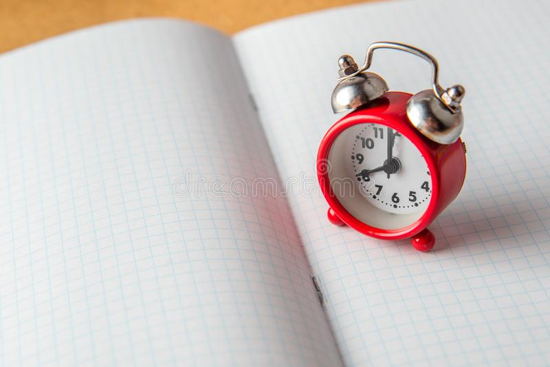 Back to school concept. old alarm clock on a clean notebook. Copy space.  royalty free stock photos