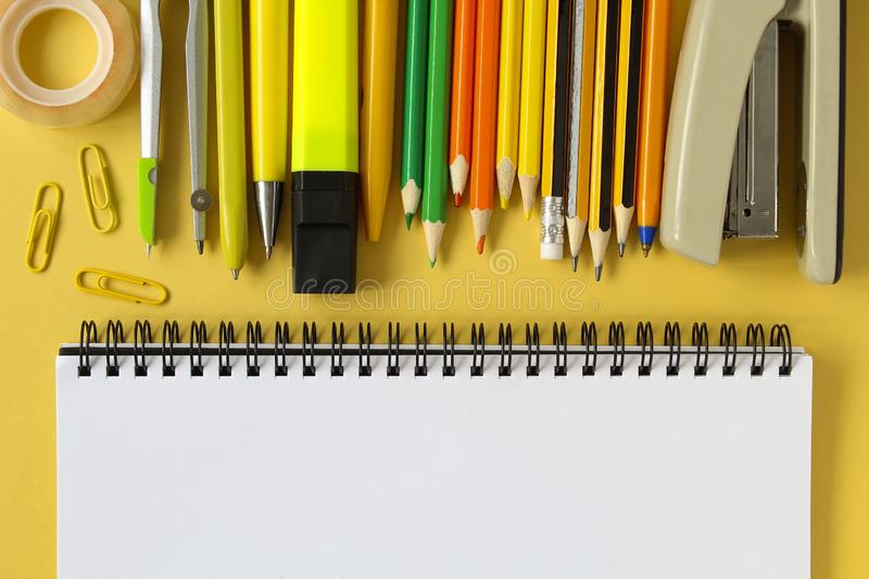 Back to school concept. Open empty mockup notebook and colored school stationery. Yellow paper background. Flat lay, top view, royalty free stock photo