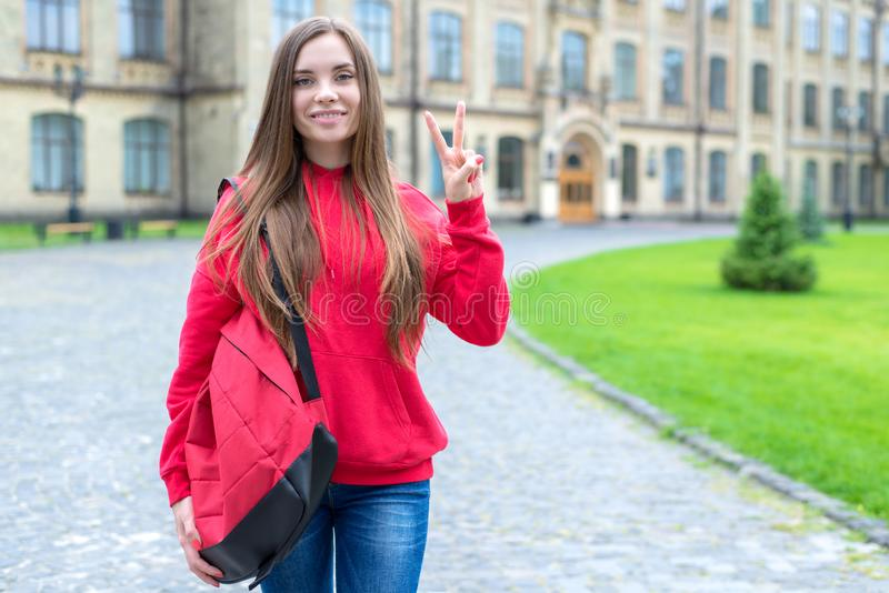 Back to school concept. Photo portrait of one in bright jeans casual clothes youngster millennial lady giving v-sign standing near. Doors of educational stock photos