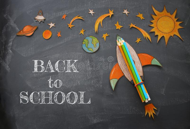 Back to school concept. rocket with pencils, space elements shapes cut from paper and painted over classroom blackboard background royalty free stock photo