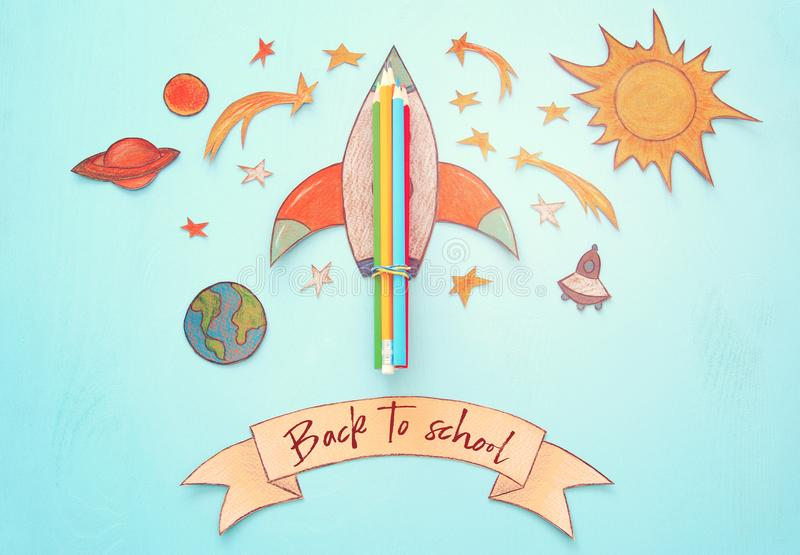 Back to school concept. rocket, space elements shapes cut from paper and painted over wooden blue background. royalty free illustration