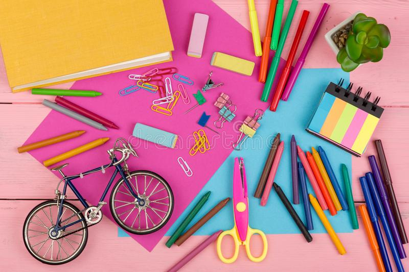 Back to school concept - school supplies: books, markers, crayons, pink and blue paper, scissors, eraser and other accessories. On pink wooden table royalty free stock photography