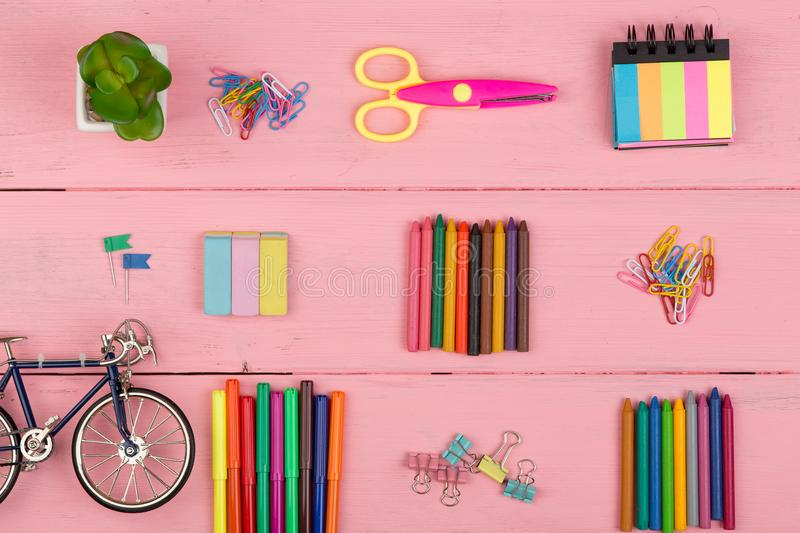 Back to school concept - school supplies: scissors, eraser, markers, crayons, little bicycle and other accessories. On pink wooden table stock photos