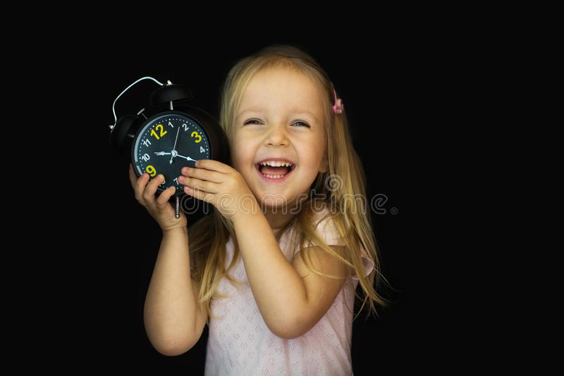 A schoolgirl with an alarm clock in hand is shocked. A small girl is surprised and looking up with a black stock image
