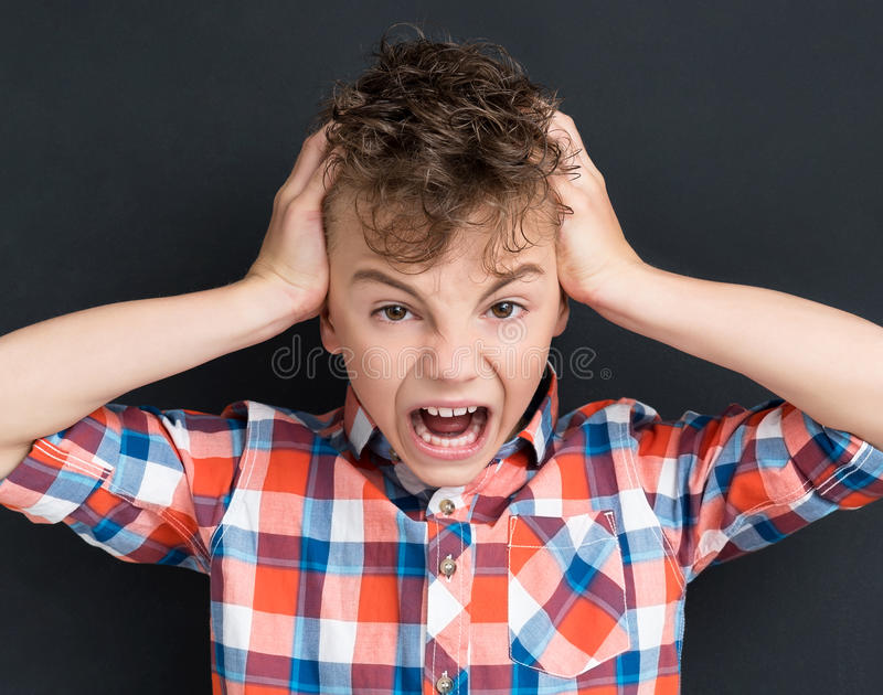 Back to school concept - shocked young boy at the black chalkboard stock photos