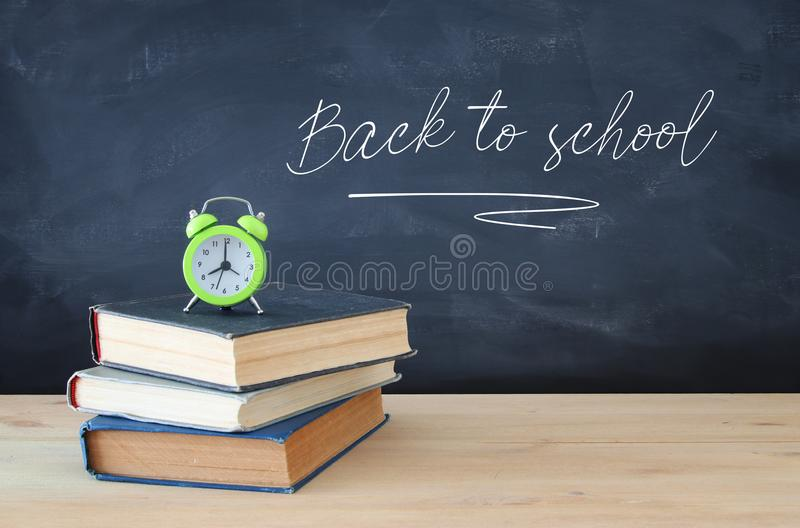 Back to school concept. stack of books and alarm clock over wooden desk in front of blackboard. royalty free stock photo