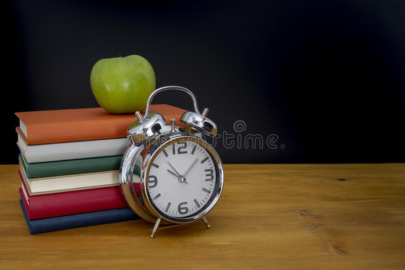 Back to school background with books and alarm clock over chalkboard stock image