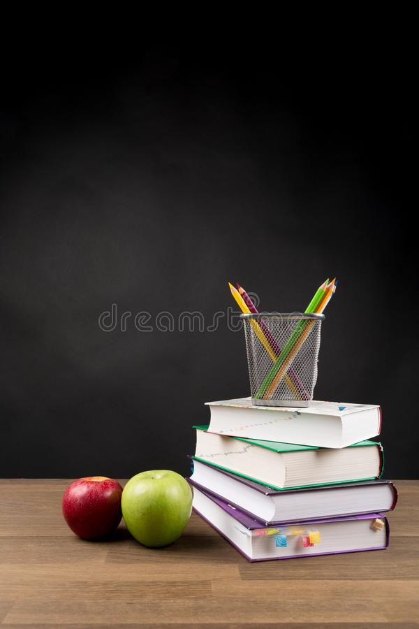 Back to School Concept, Stacked books, Coloring Pencils and red and green apple isolated on black blackboard background stock image