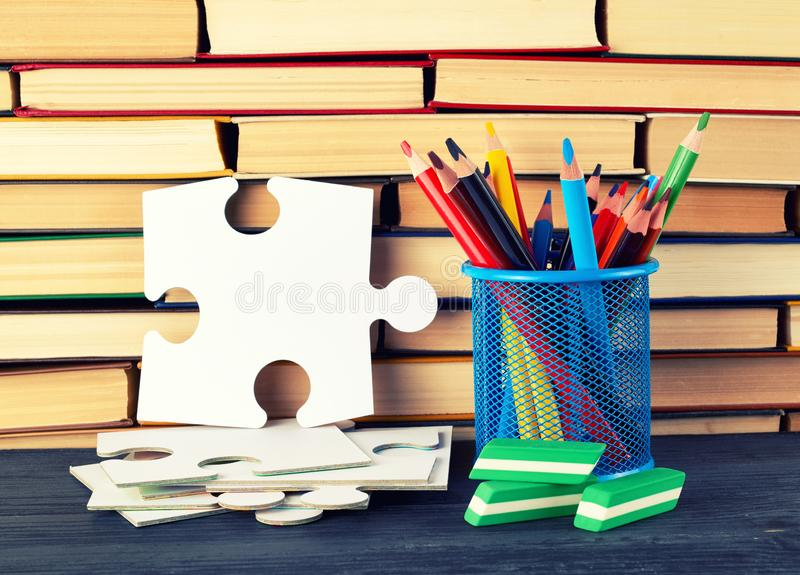 Back to school concept. Stacks of various hardback books and blue stationery glass with multi-colored wooden pencils, back to school concept royalty free stock images