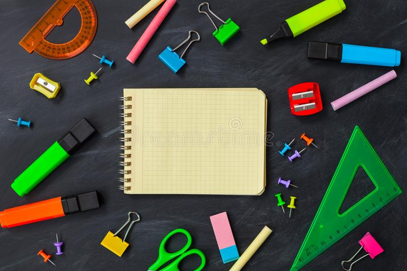 Back To School concept. School supplies on blackboard background royalty free stock image