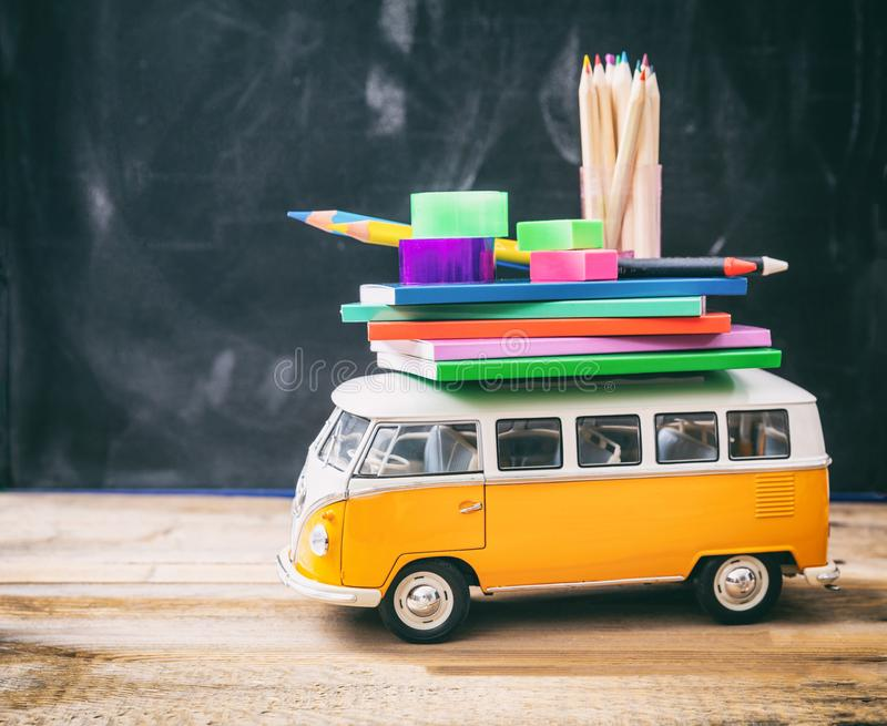 School supplies and school bus on wooden desk, blackboard background royalty free stock photos