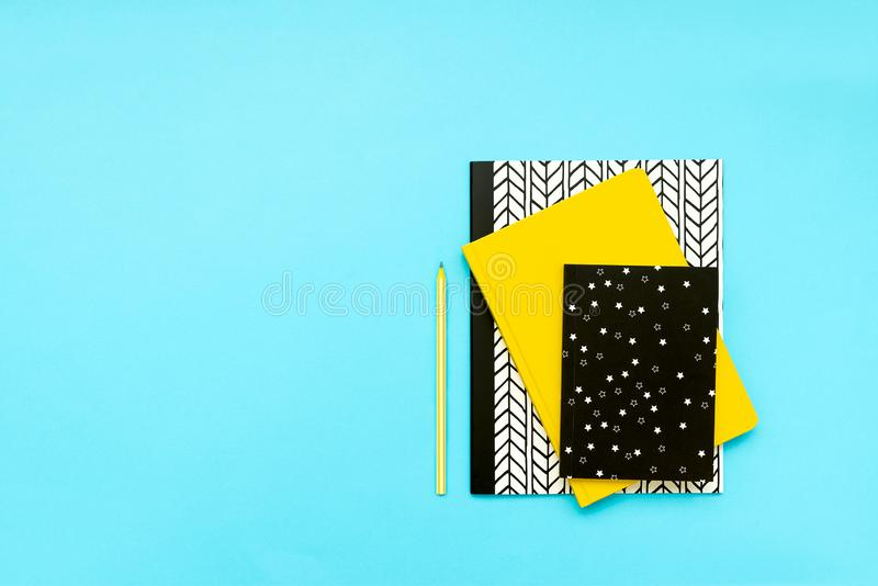 Back to school concept. School supplies: notebooks and pens on blue background. Top view. Copy space. Flat lay.  royalty free stock photography