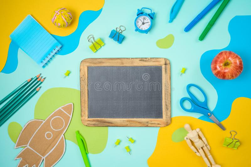 Back to school concept with school supplies and paper flowing shapes background. Top view from above stock images