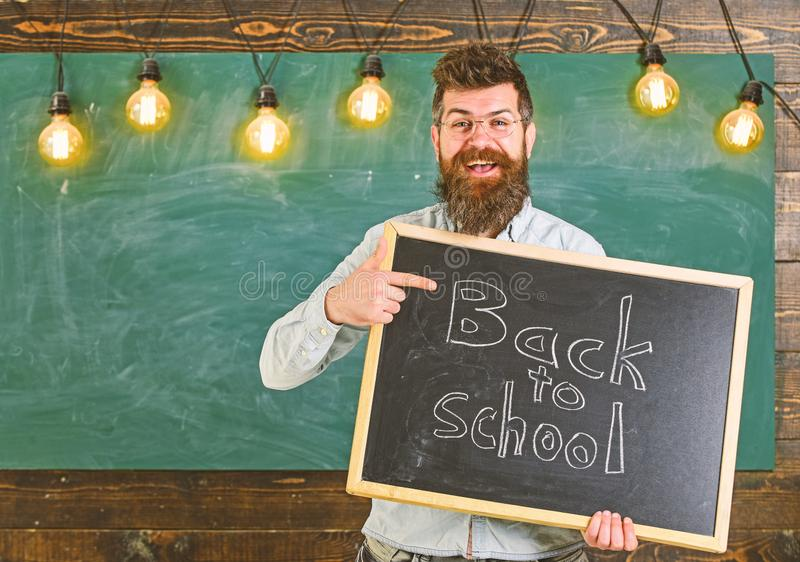 Back to school concept. Teacher in eyeglasses holds blackboard with inscription back to school. Man with beard and. Mustache on cheerful face welcomes students royalty free stock photos