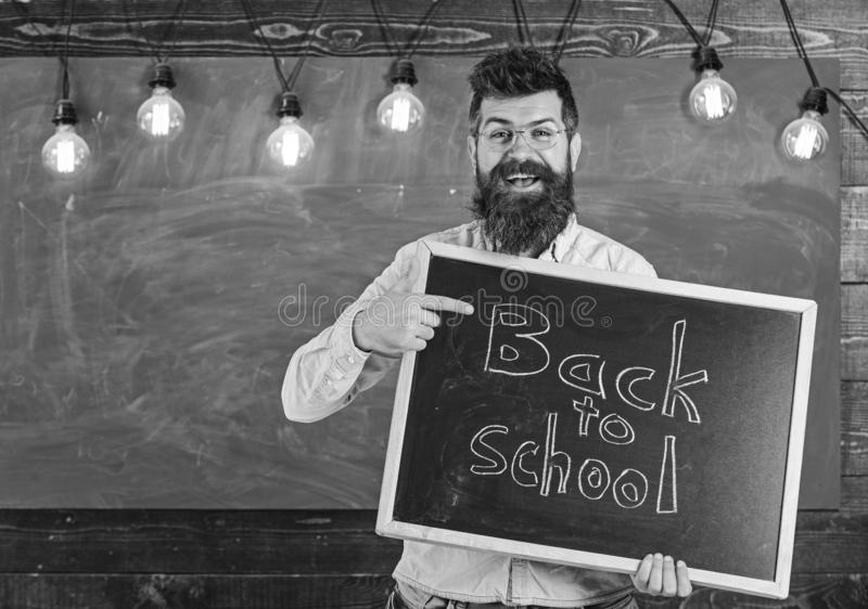 Back to school concept. Teacher in eyeglasses holds blackboard with inscription back to school. Man with beard and. Mustache on cheerful face welcomes students royalty free stock photo