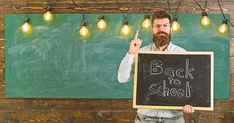 Back to school concept. Teacher in eyeglasses holds blackboard with inscription back to school. Man with beard and. Mustache on strict face warns students stock photo