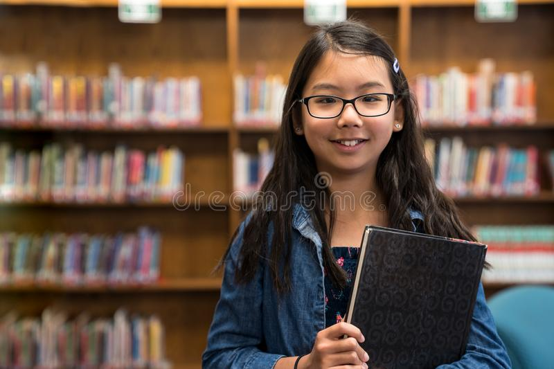 Asian teenage girl with eyeglasses in school library royalty free stock image
