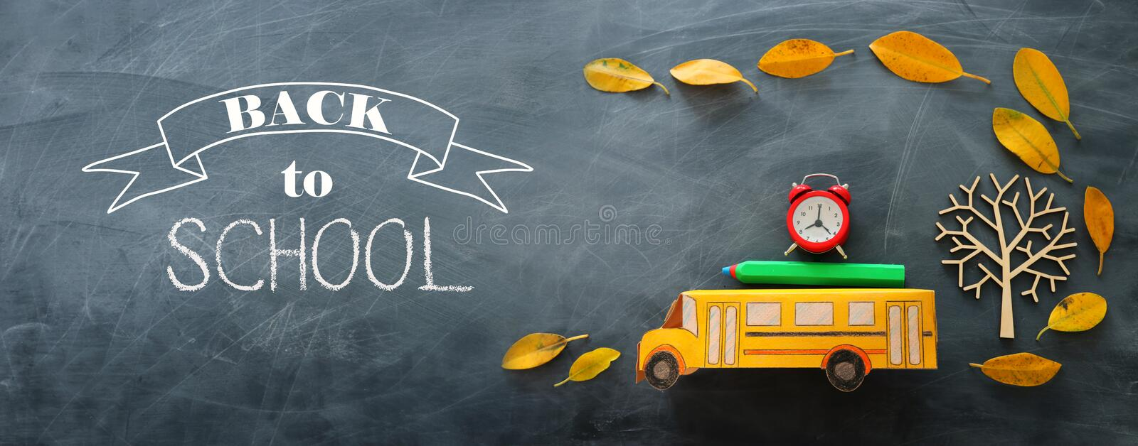 Back to school concept. Top view banner of school bus, alarm clock and pencil next to tree with autumn dry leaves over classroom. Blackboard background stock images