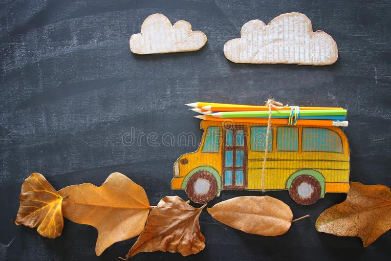 Back to school concept. Top view image school bus and pencils over autumn dry leaves classroom blackboard background. stock image