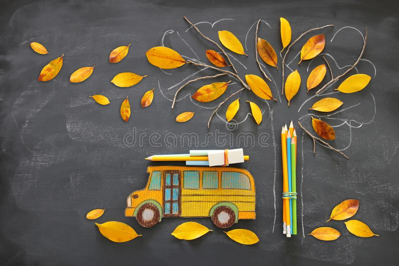 Back to school concept. Top view image of school bus and pencils next to tree sketch with autumn dry leaves over classroom blackbo royalty free illustration
