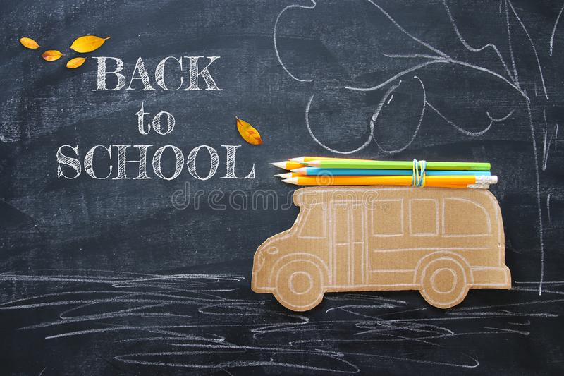 Back to school concept. Top view image school bus and pencils over classroom blackboard background. stock illustration