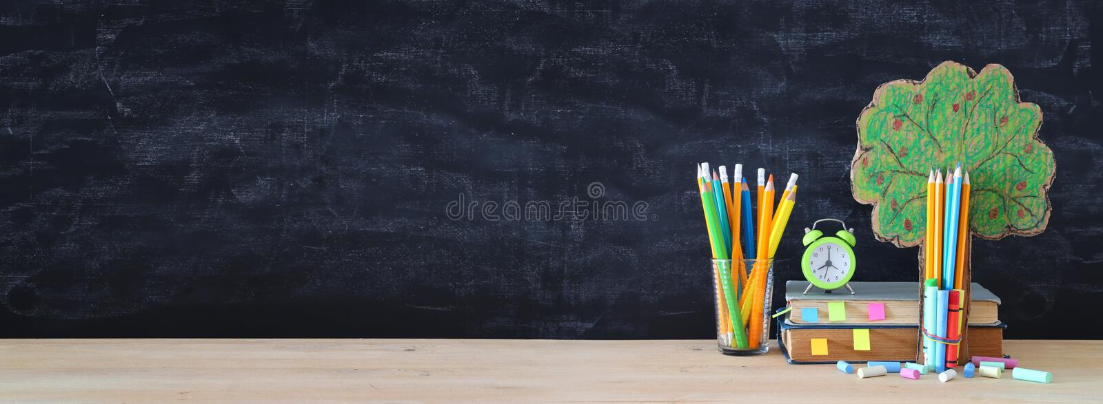 Back to school concept. tree of knowledge and pencils in front of classroom blackboard. royalty free illustration