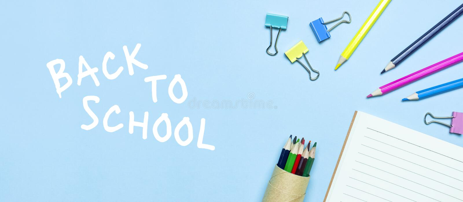 Back to school concept. Wooden colored pencils, clean school notebook in line, paper clips on blue background top view flat lay stock photo