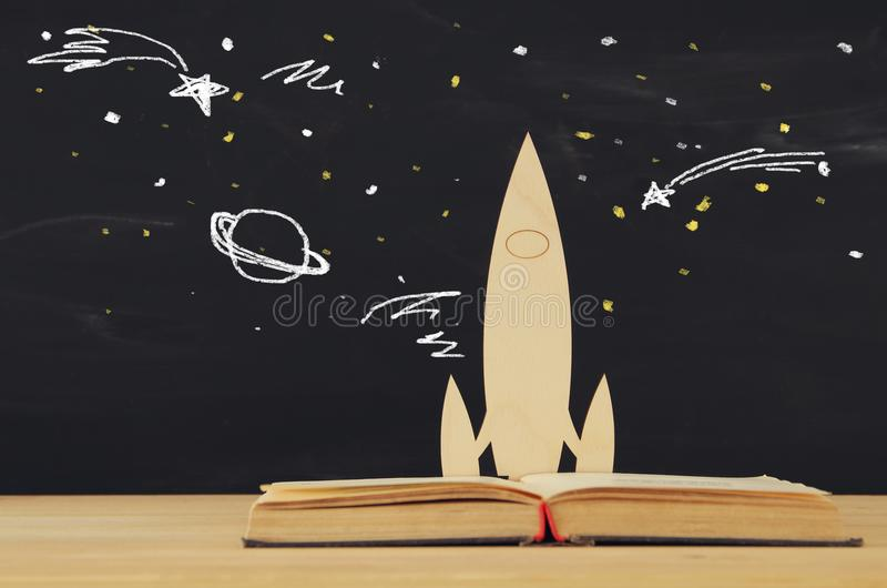 Back to school concept. wooden rocket and space sketchs over open book in front of classroom blackboard. royalty free stock image