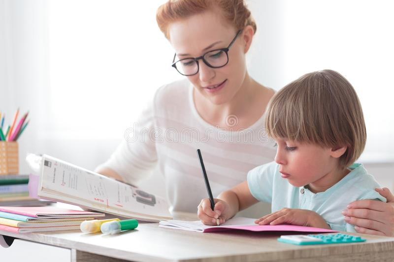Mother helping son with homework stock photography