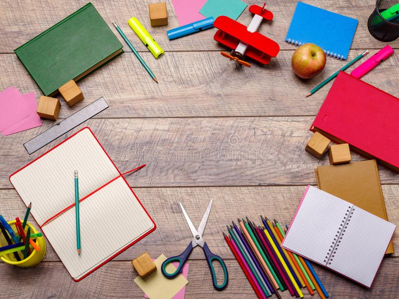 Desk with school supplies against wooden background stock photography