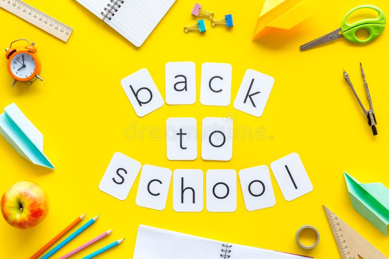 Back to school copy with stationary, apple, notebook and alarm clock on yellow student desk background top view royalty free stock photo