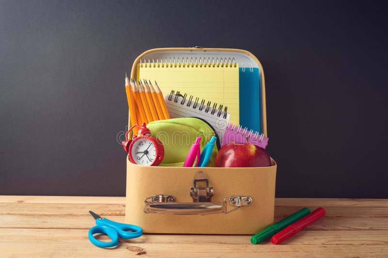 Back to school creative background with cardboard suitcase and school supplies on wooden table. Sale concept royalty free stock photos
