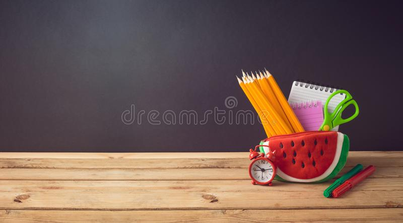 Back to school creative background with watermelon pencil case and school supplies on wooden table stock photo