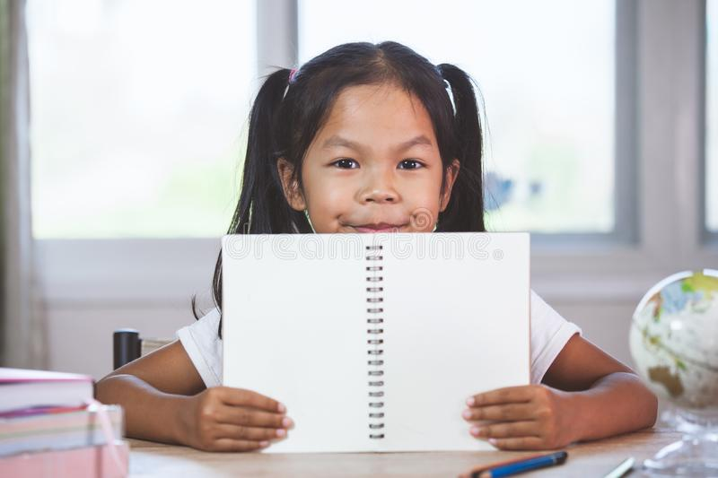 Back to school. Cute asian child girl holding a book stock images