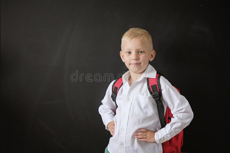 Back to school. Cute little boy at blackboard. Child from elementary school with bag. Education concept. stock photos