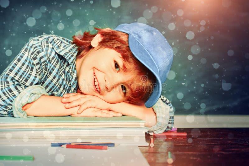 Back to school. Cute little preschool kid boy in a classroom. Schoolchild. Happy mood smiling broadly in school. Schoolboy. Elementary school and education stock photos