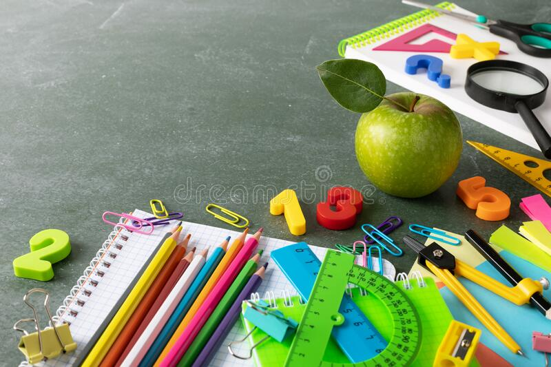Back to school and education background with colorful stationery supplies and fresh green apple on empty school blackboard royalty free stock images
