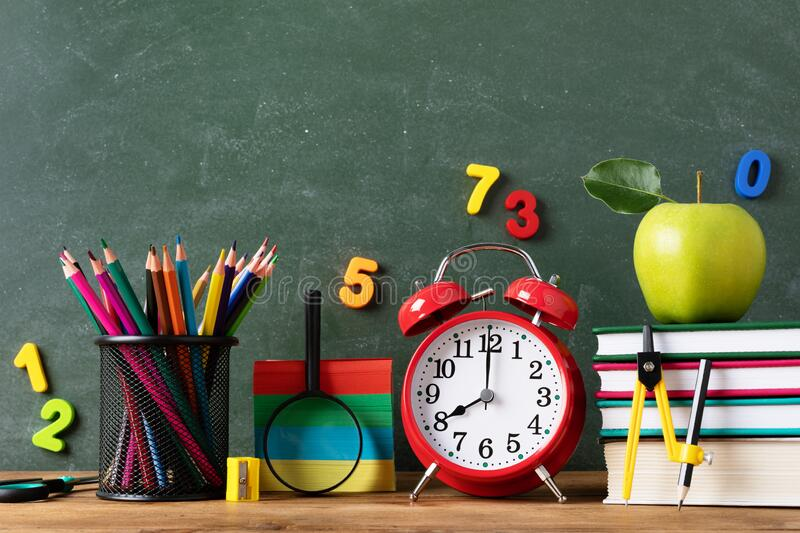 Back to school or education concept with alarm clock, school supplies and fresh green apple against blackboard background royalty free stock photography
