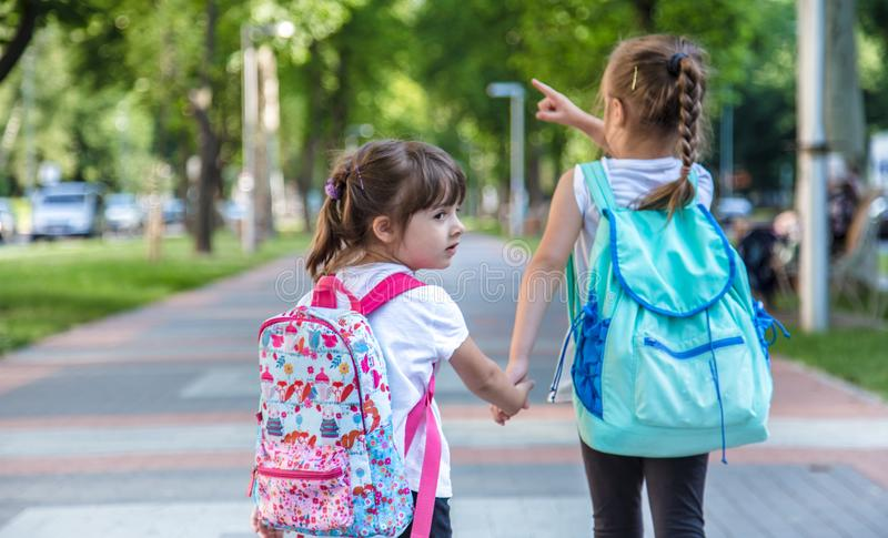 Back to school education concept with girl kids, elementary students, carrying backpacks going to class royalty free stock photo