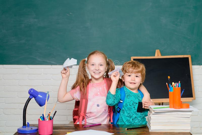 Back to school - education concept. Kids with a paper airplane. Girl and boy with happy face expression near desk with royalty free stock images
