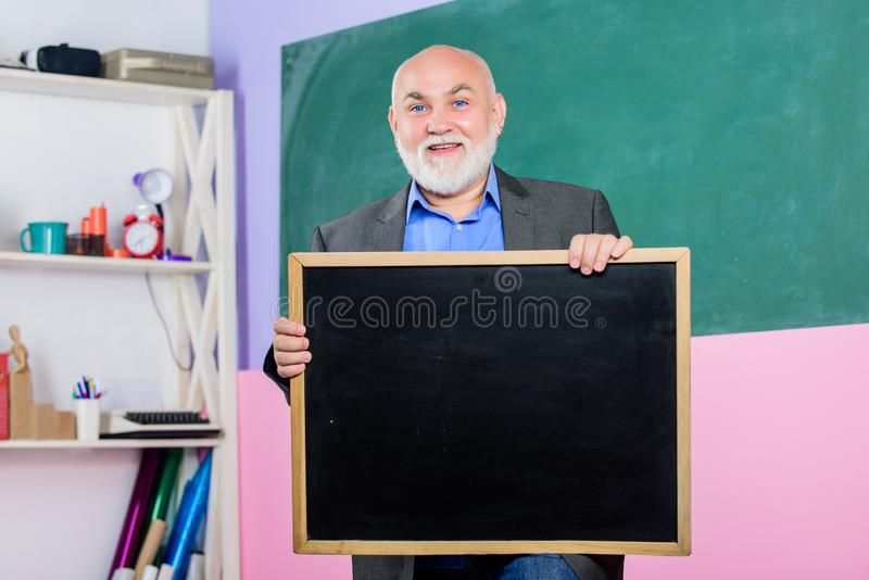 Back to school. Education concept. place for copy space. Mature teacher man hold chalk board. information is here. exam. And graduation results. senior man royalty free stock photos