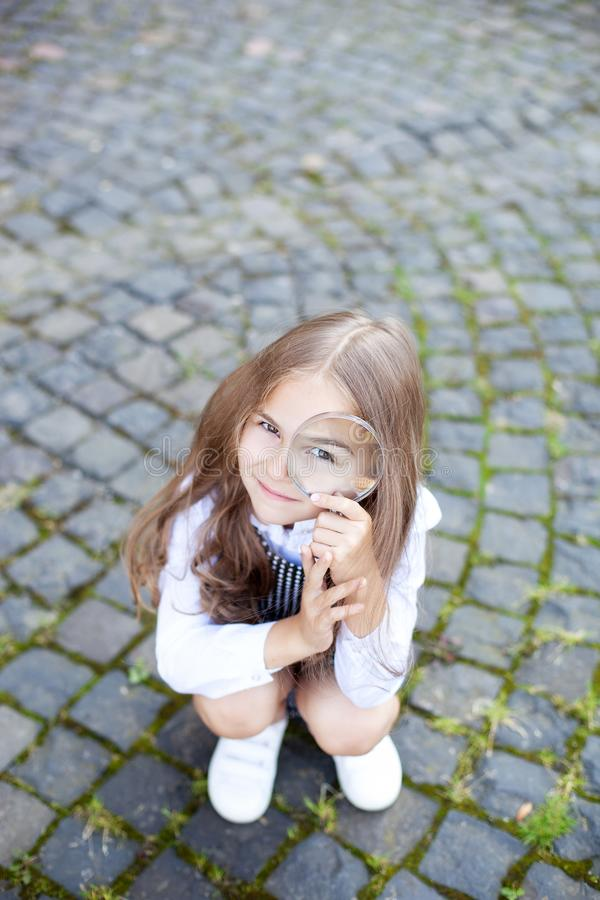 Back to school. Education concept. Preschool education. Funny little girl looking through a magnifying glass. Little detective. in. Vestigation, discovery and stock images