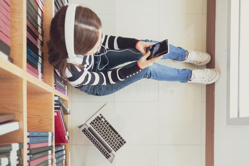 Back to school education knowledge college university concept, Female student study in library using tablet and searching internet. While Listening music and stock image