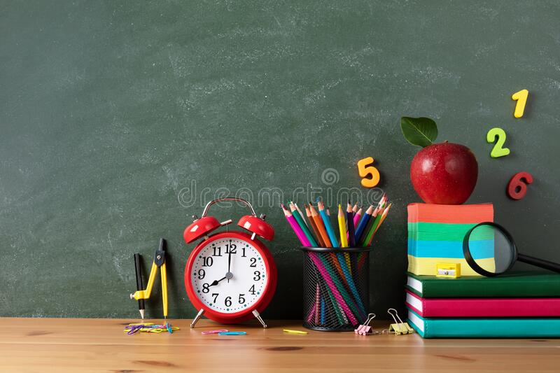 Back to school or education mockup with alarm clock, red apple and stationery supplies against blackboard on wooden table. stock photos
