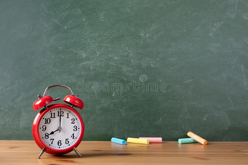 Back to school or education template with alarm clock and colorful chalks against empty blackboard background in classroom. stock images
